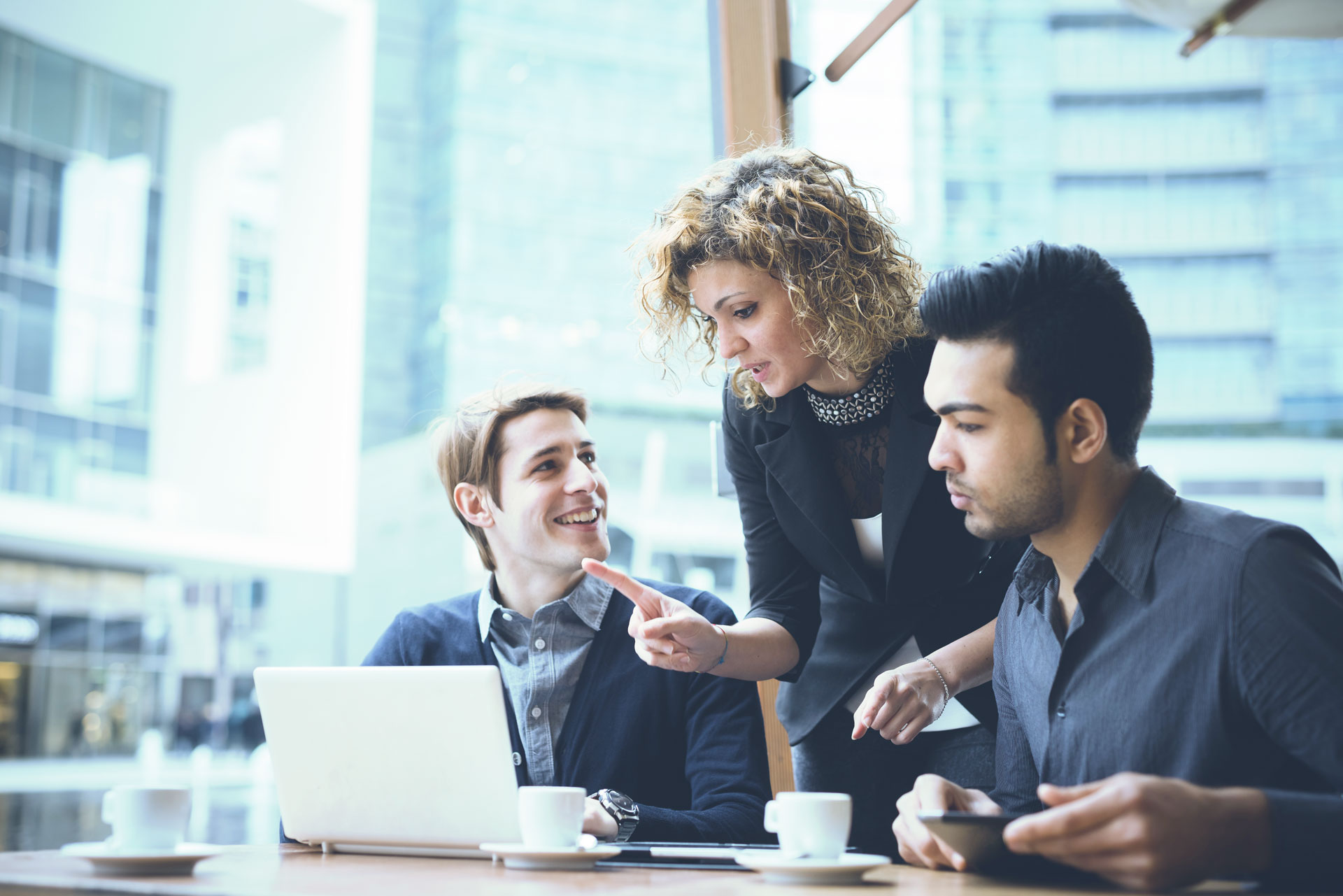 Multiracial contemporary business people working connected with technological devices like tablet and laptop, talking together - finance, business, technology concept.